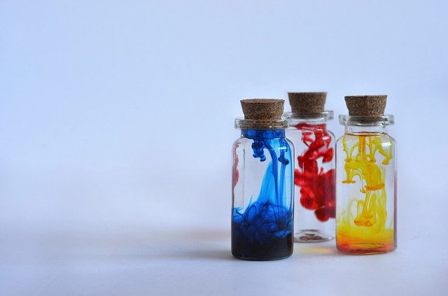 Liquid epoxy resin dye & alcohol inks of many colors in bottles.
